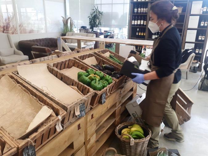 Una empleada de Semonia coloca hortalizas en el expositor de la nueva tienda